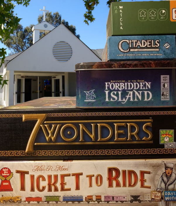 Stack of board games in front of Heritage Presbyterain Church. Includes Matcha, Citadels, Forbidden Island, 7 Wonders, and Ticket to Ride.